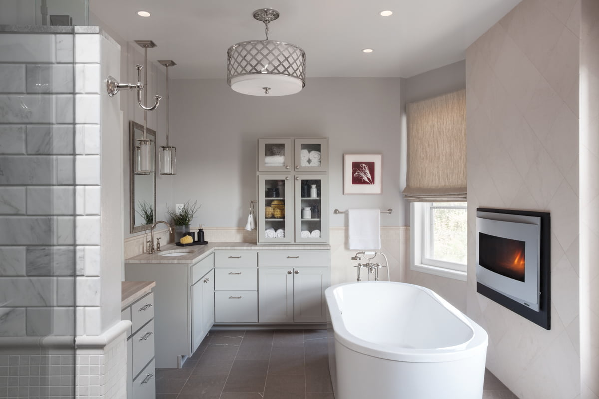 A soaking tub in the master bath is flanked by a gas fireplace.