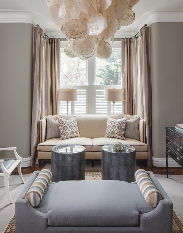 A chandelier by Oly makes a statement in the living room.